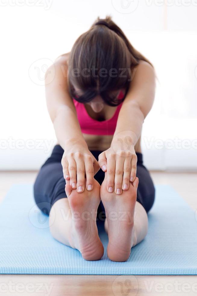mooie gezonde jonge vrouw die oefening thuis doet. foto