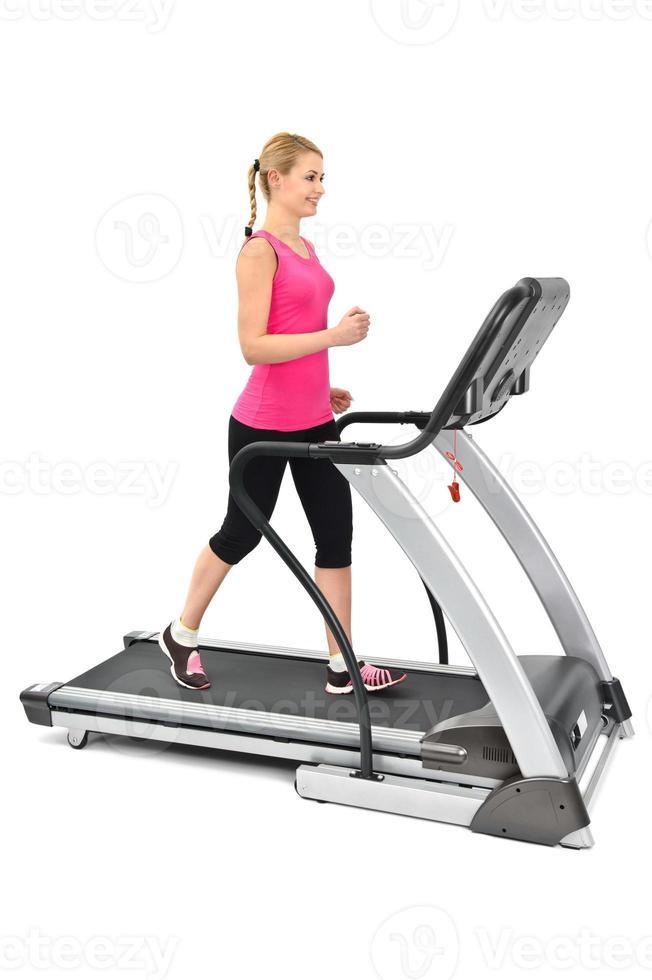 een jonge vrouw in roze joggen op een standaard loopband foto