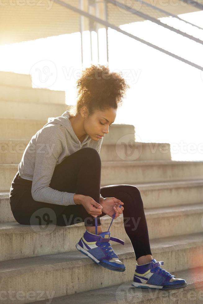 jonge oefeningsvrouw die haar schoenveters bindt foto