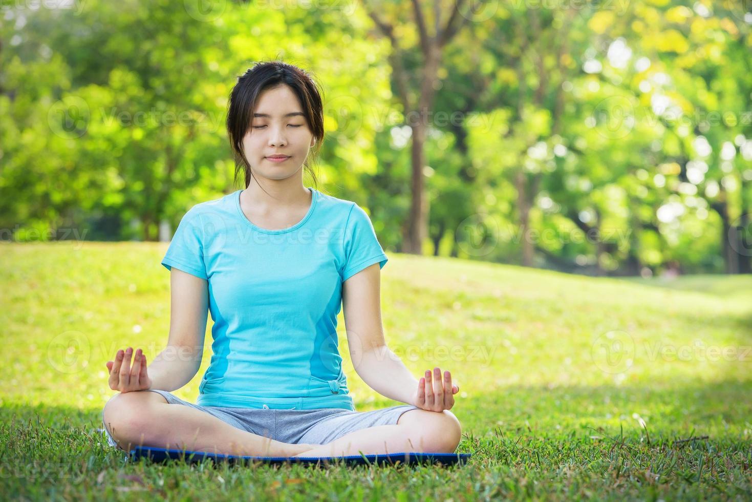 jonge vrouw die yogaoefeningen doet openlucht foto