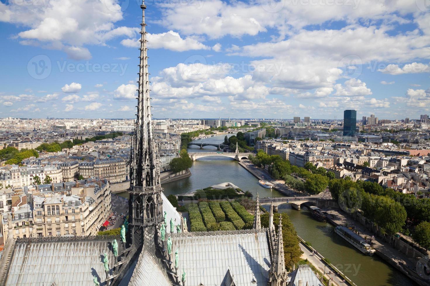 de torenspits van de notre dame over de skyline van parijs foto
