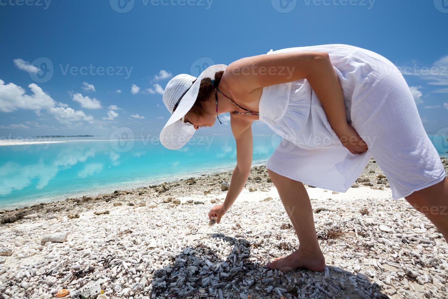 blanke vrouw verzamelen schelpen op het strand foto