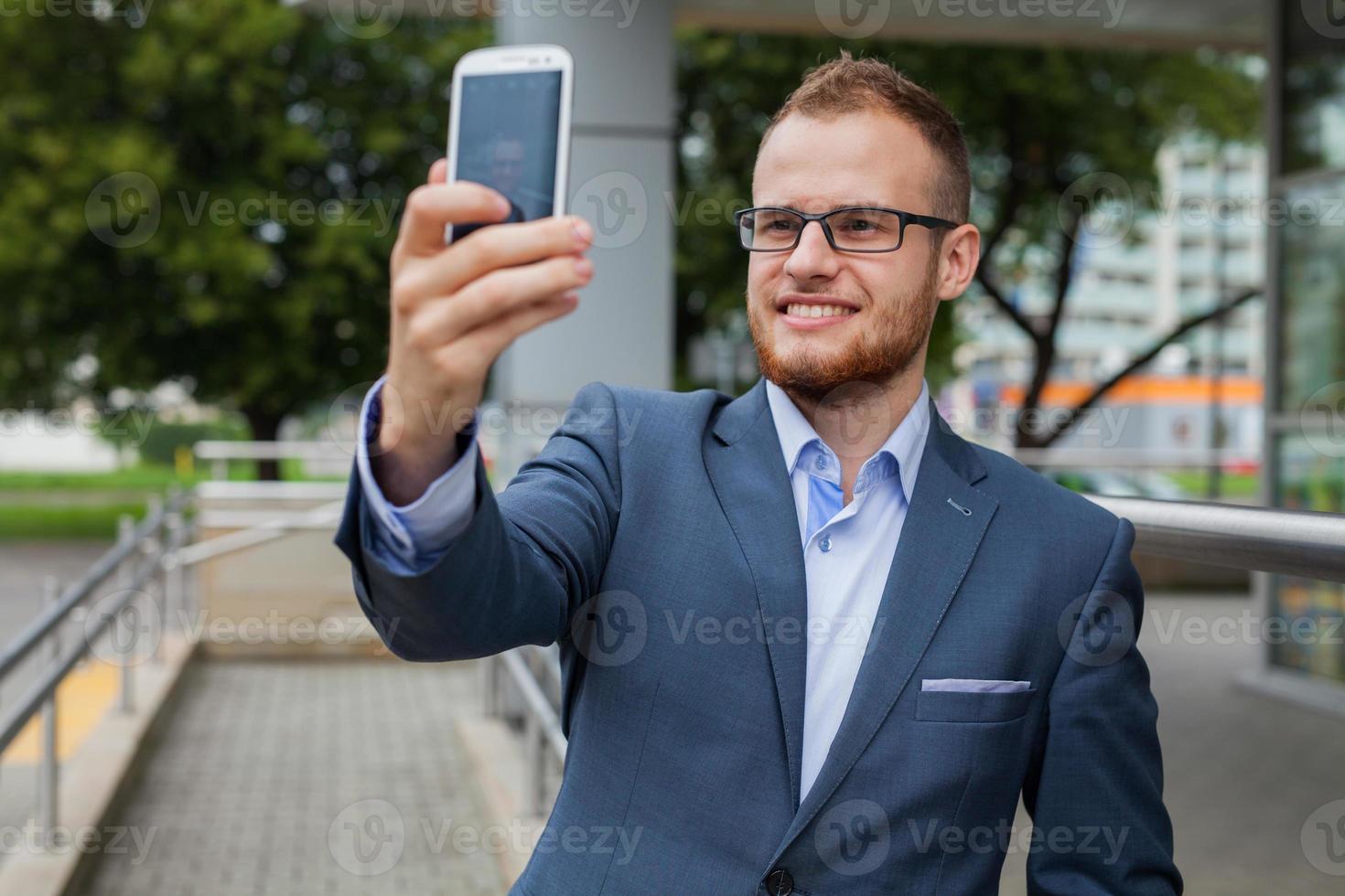 Kaukasische zakenman buiten kantoor met behulp van mobiele telefoon. foto