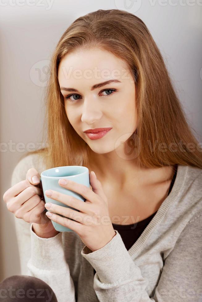 mooie casual blanke vrouw zitten met warme dranken. foto