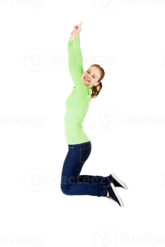 jonge gelukkig blanke vrouw springen in de lucht foto