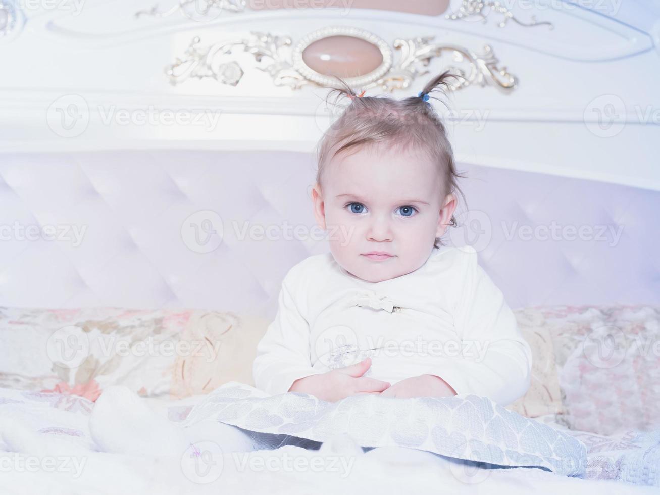 kleine blanke kind meisje, zittend op het bed thuis foto