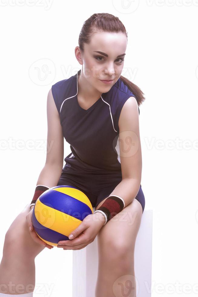Kaukasische vrouwelijke professionele volleybal atleet zitten en houden bal foto