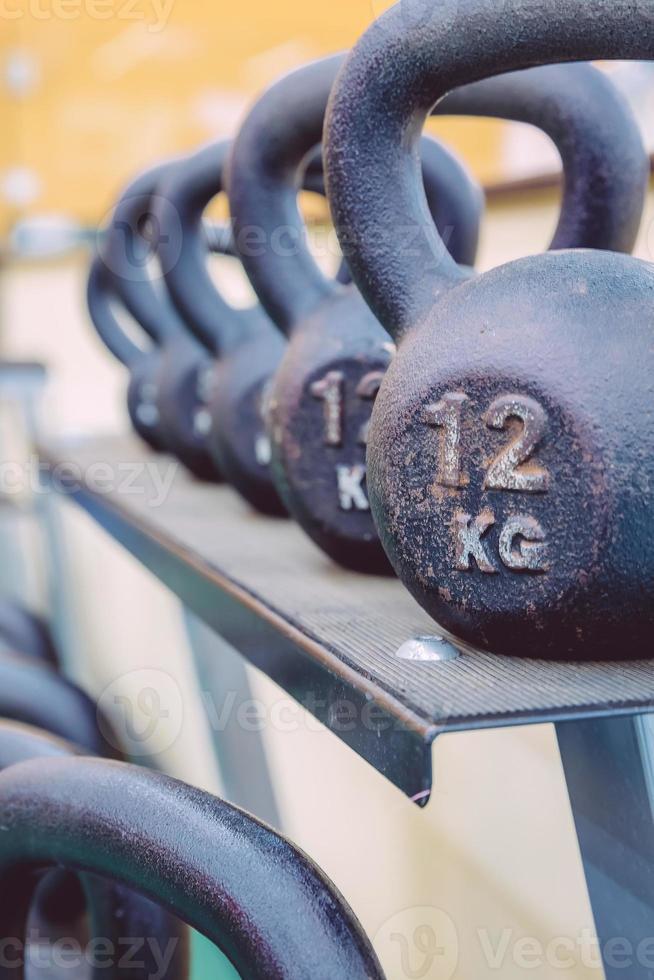 kettlebells rijen met verschillende gewichten in het fitnesscentrum foto