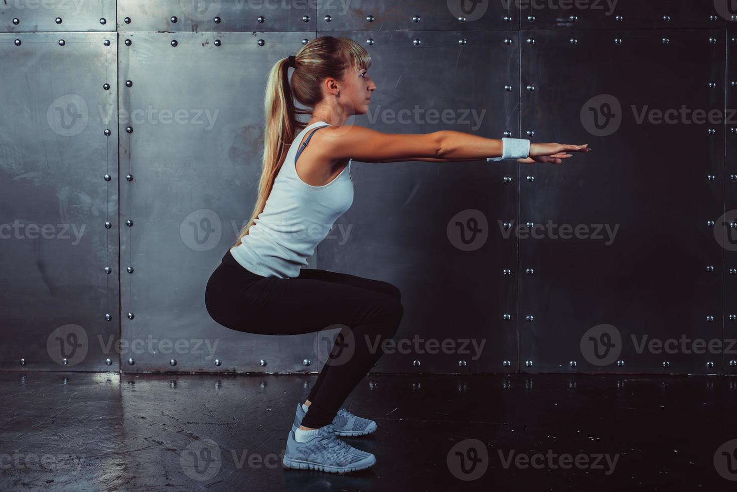 atletische jonge vrouw fitness model warming-up doen squats oefening foto