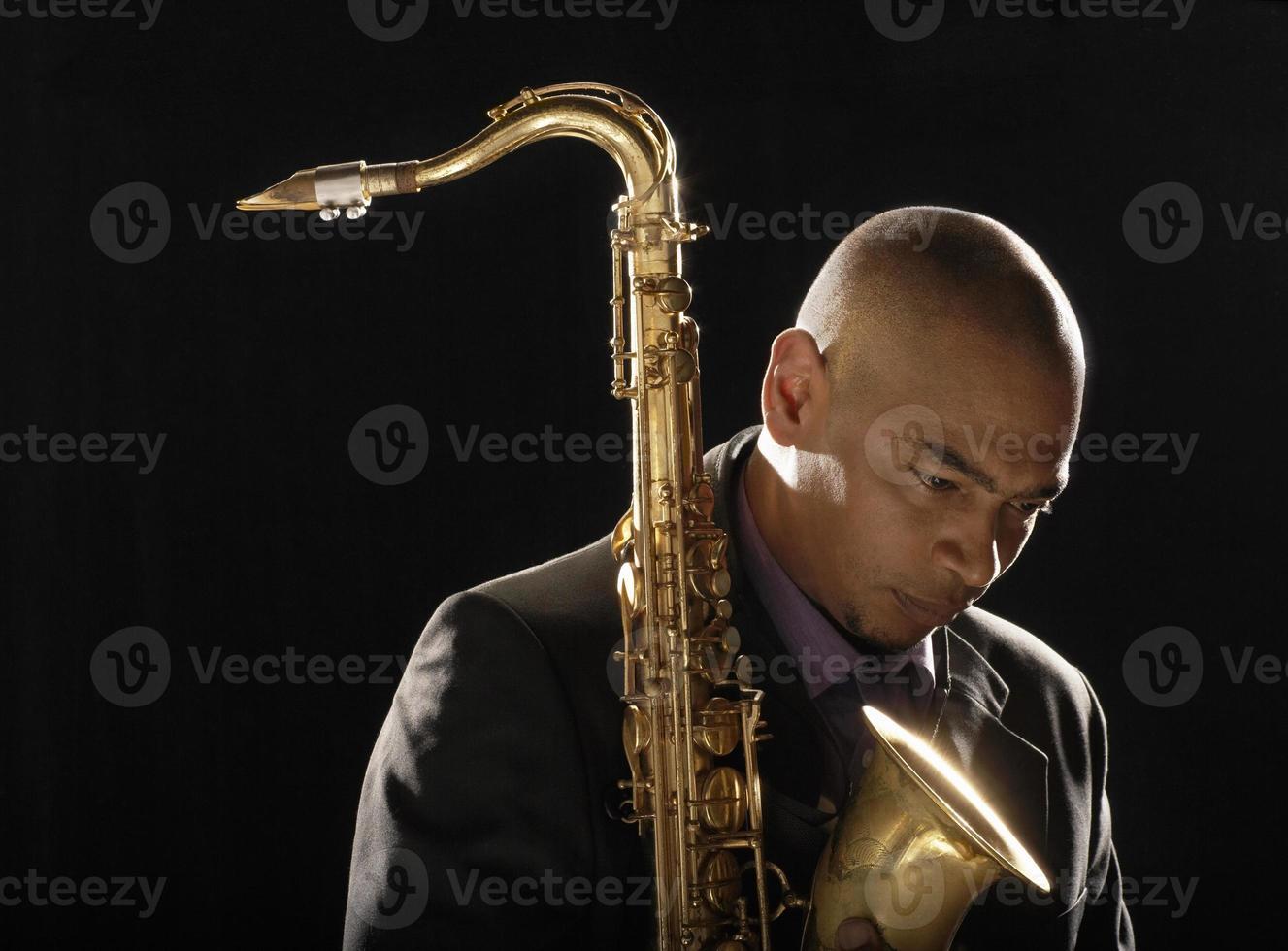 nadenkend man met saxofoon naar beneden te kijken foto