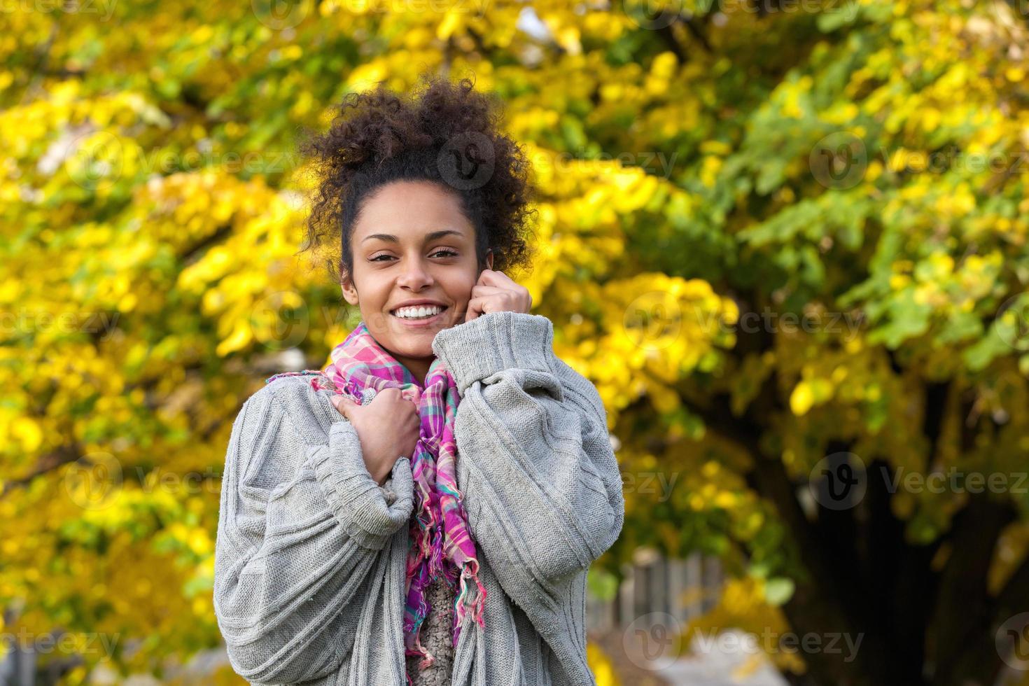 mooie Afro-Amerikaanse vrouw die lacht in de herfst foto