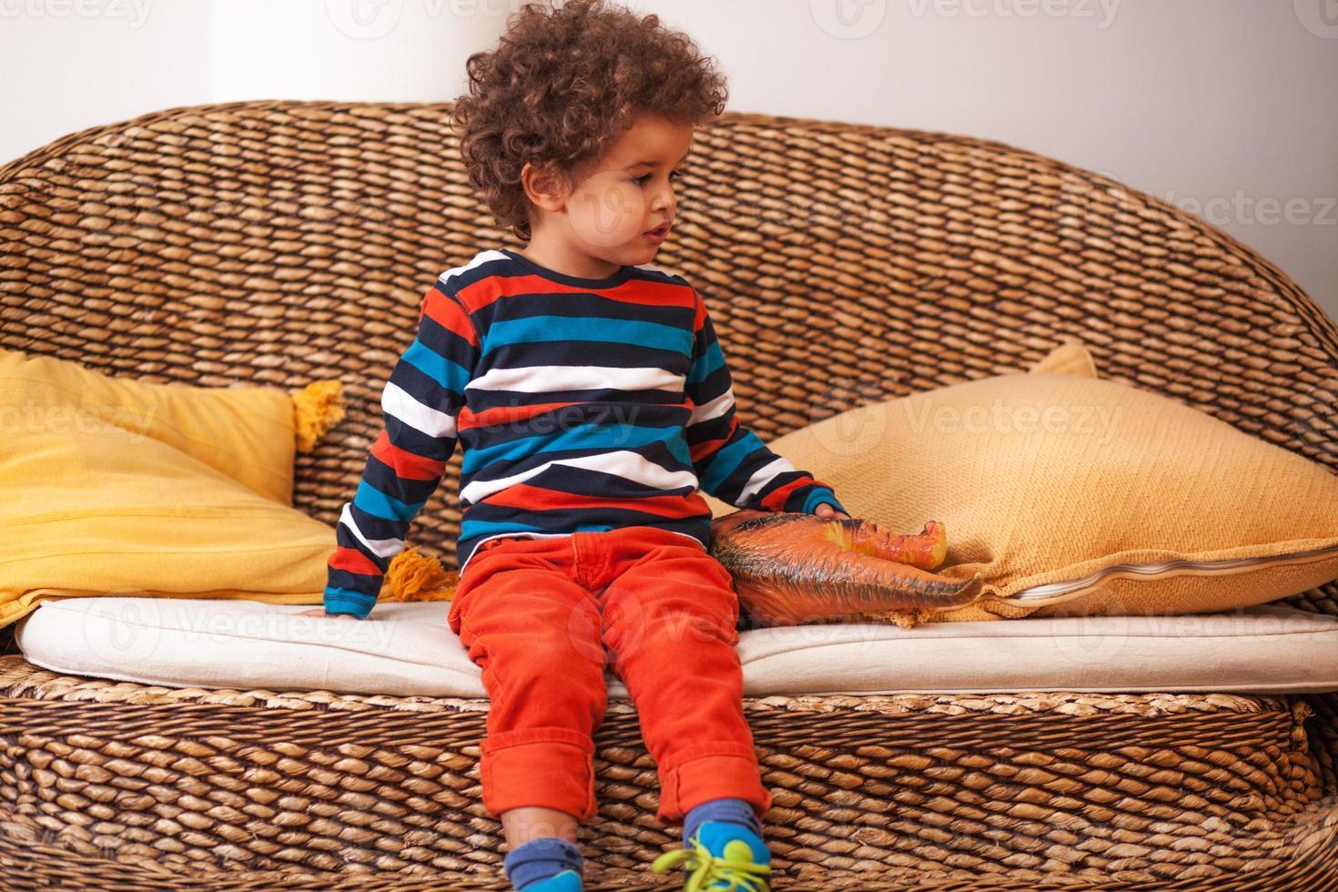 schattige jongen zit in een woonkamer foto