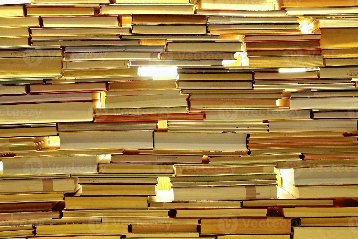 stapels boeken die een muur vormen met doorzichtige gaten foto