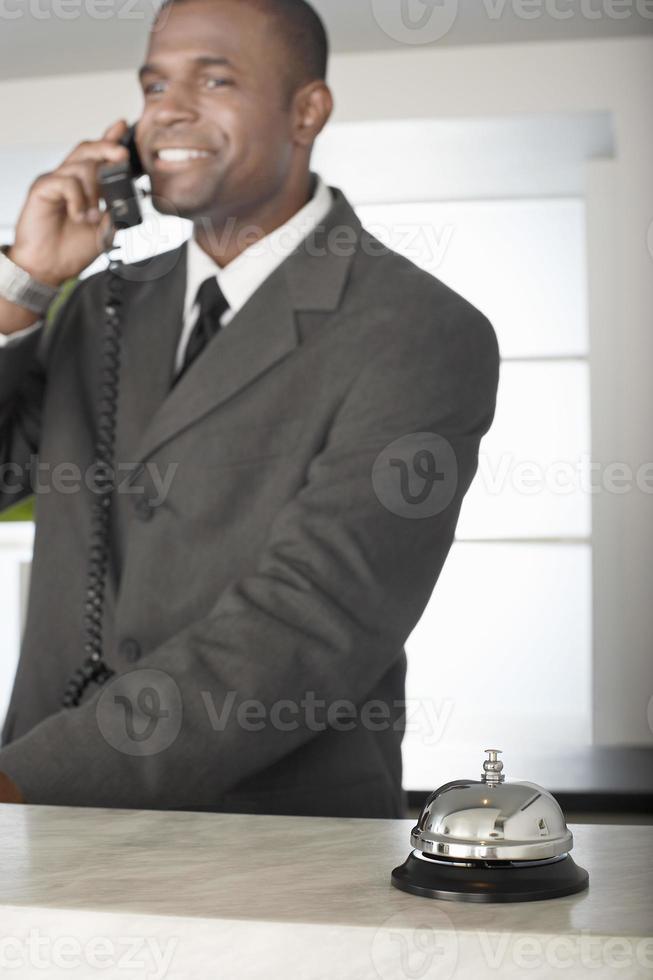 zakenman aan de telefoon bij de receptie van het hotel foto