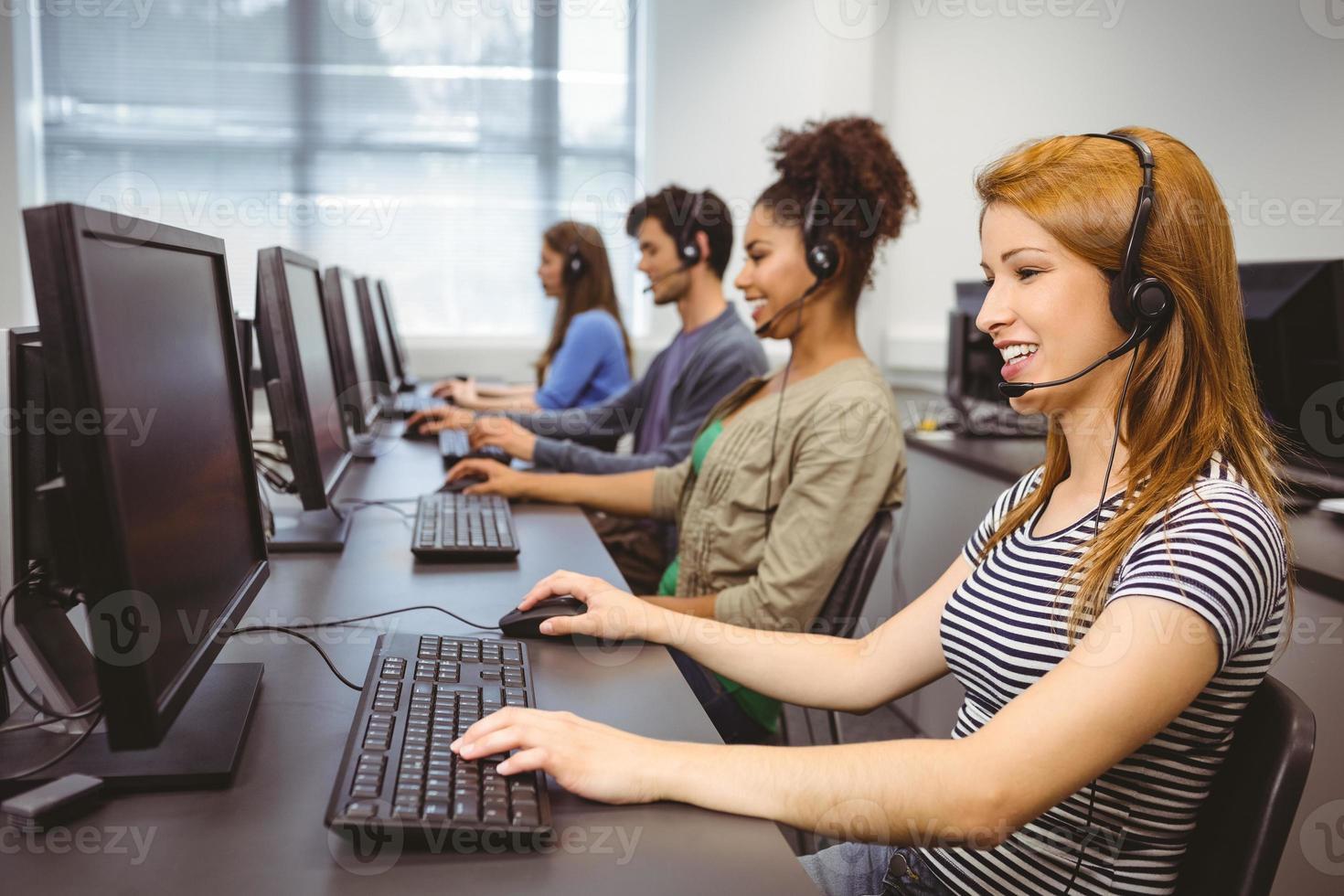lachende student achter de computer zit foto
