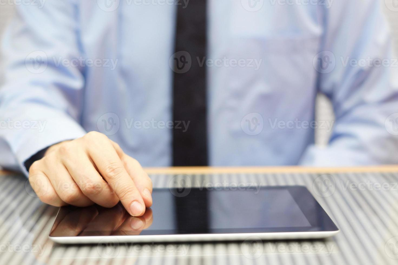 zakenman die tabletcomputer op bureau met behulp van foto