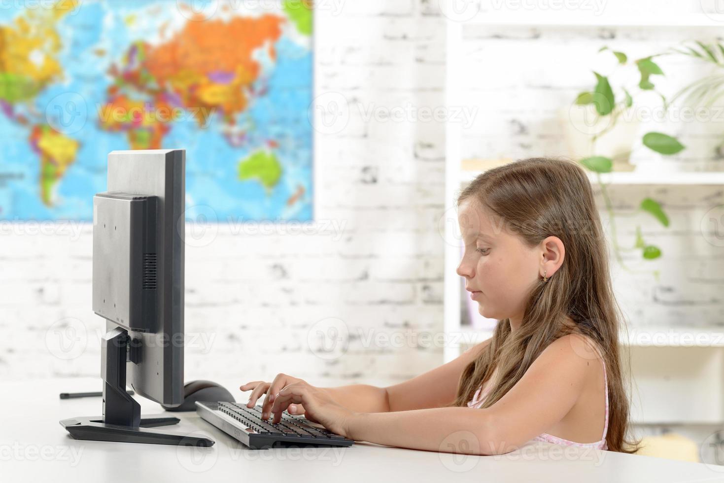 schoolmeisje met een computer in de klas foto