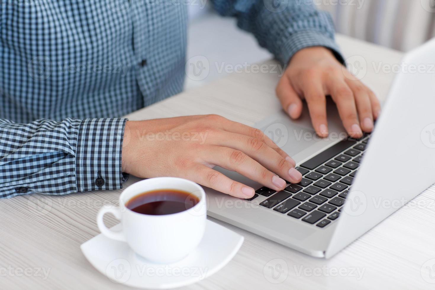 man te typen op een laptop toetsenbord op kantoor foto