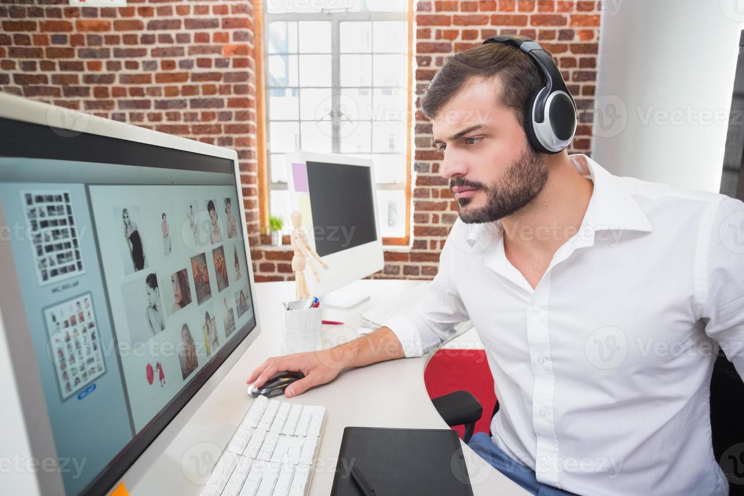 geconcentreerde fotoredacteur die computer in bureau met behulp van foto