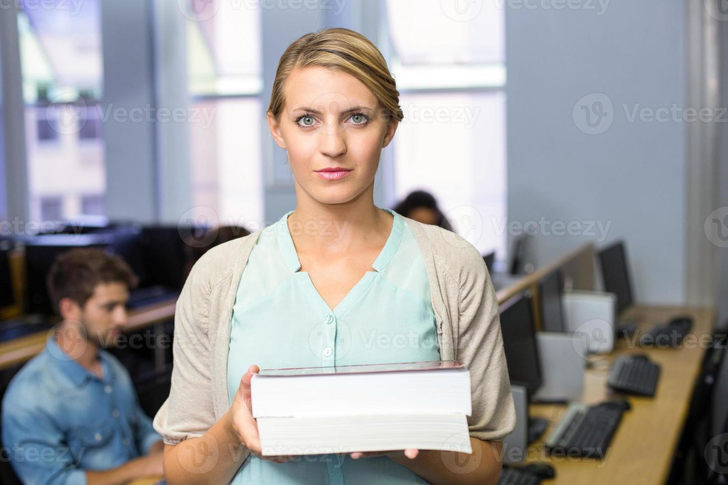 vrouwelijke leraar die boeken in computerklasse houdt foto