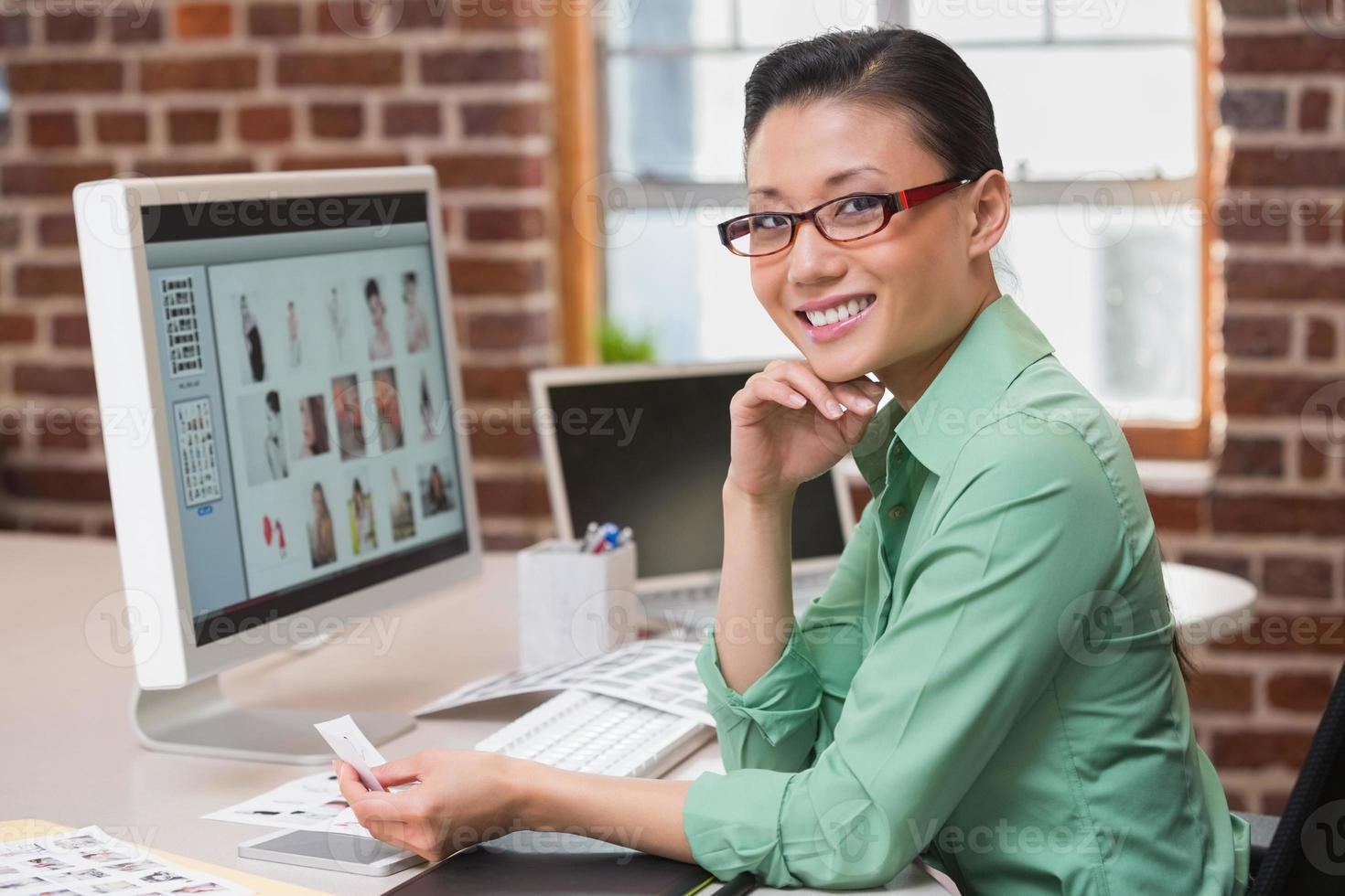 glimlachende vrouwelijke fotoredacteur die computer in bureau met behulp van foto