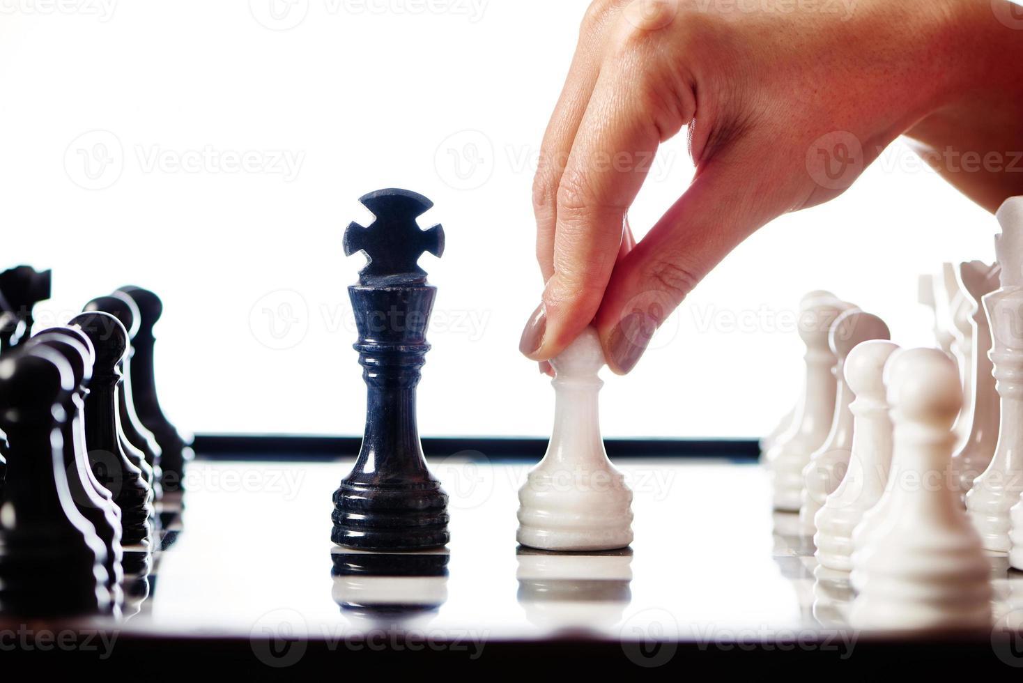 hand met witte pion gaat naar zwarte koning foto