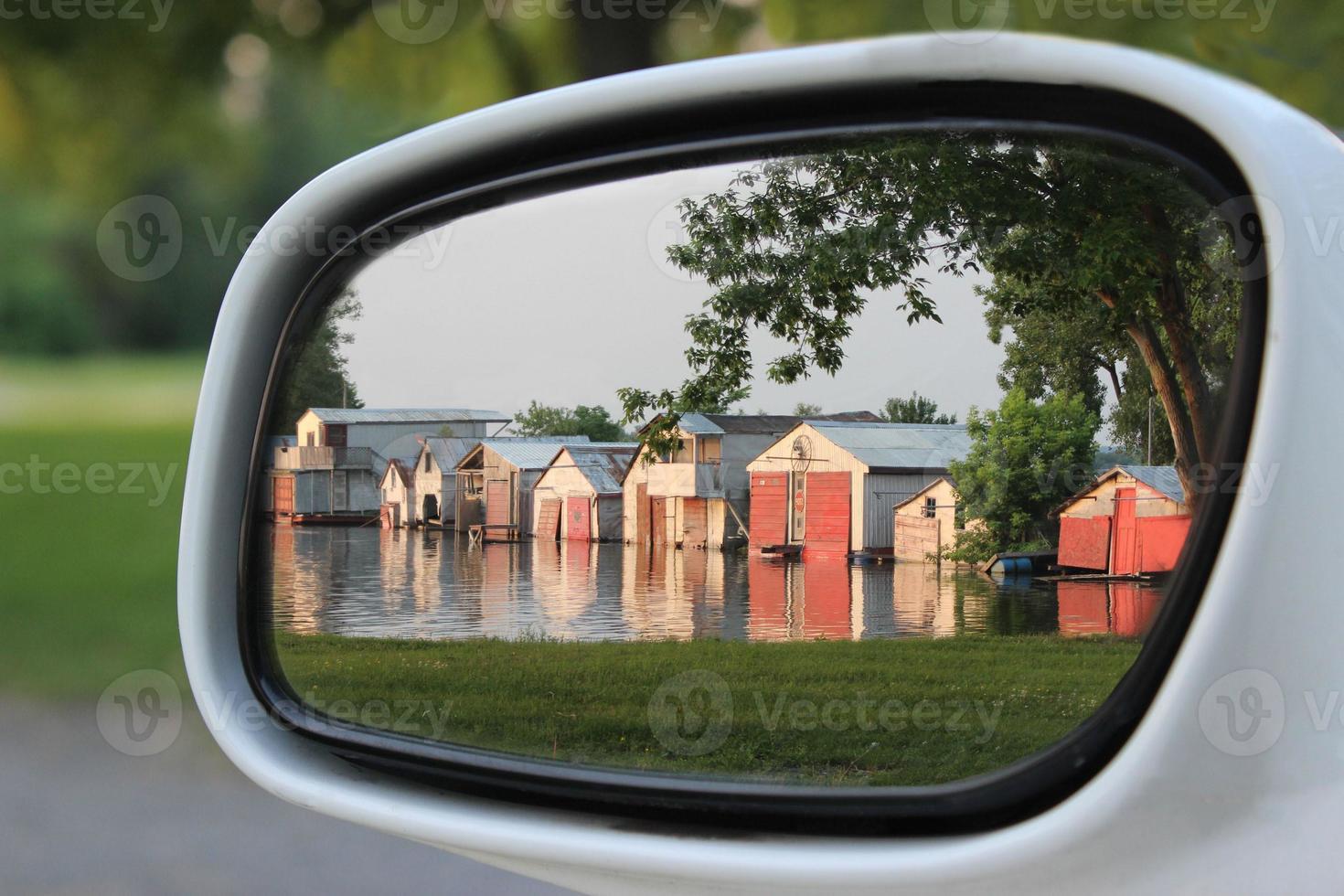 weerspiegeling in zijspiegel van auto, van botenhuizen weerspiegeld in water foto