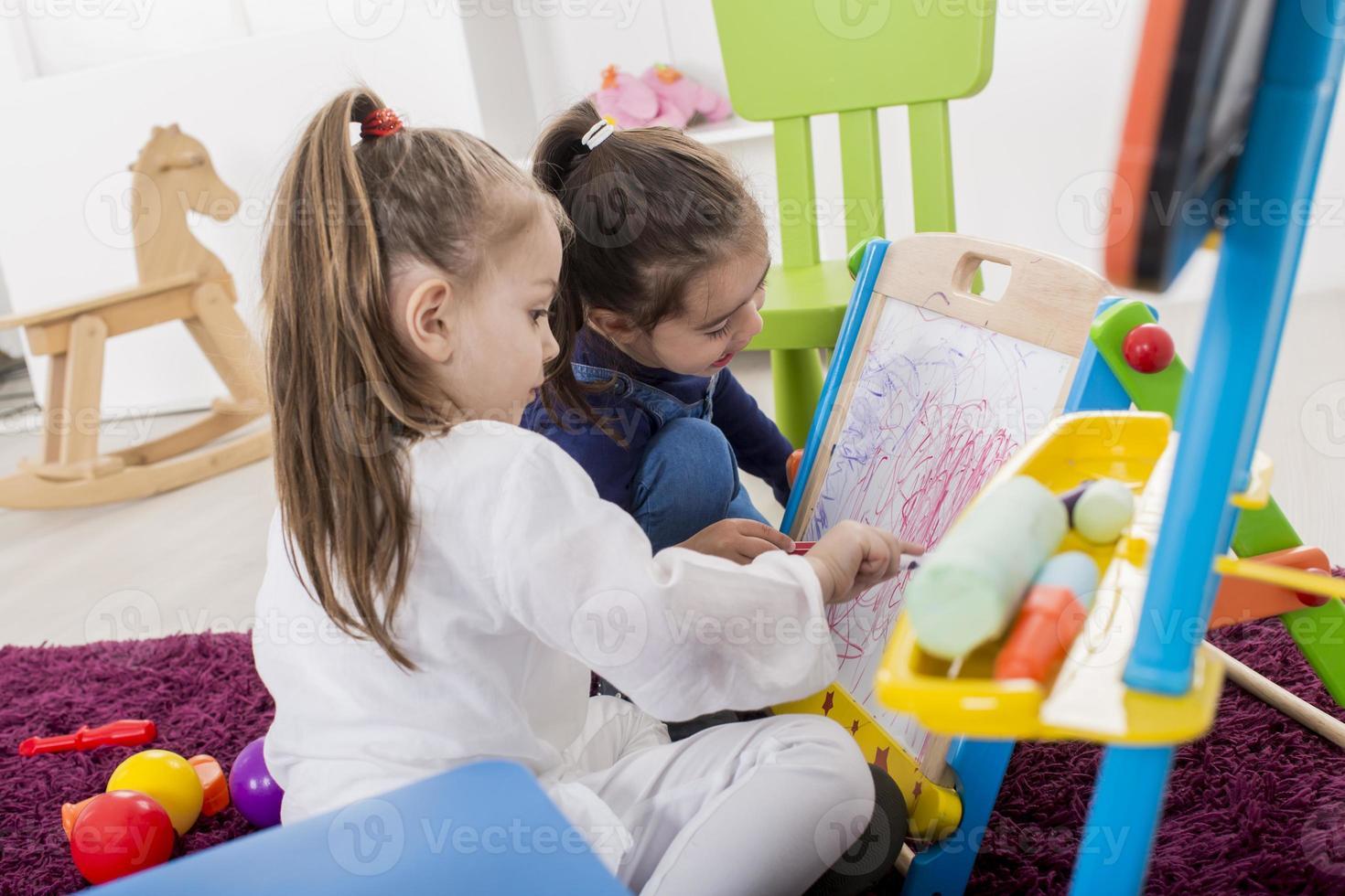 kleine meisjes tekenen in de kamer foto