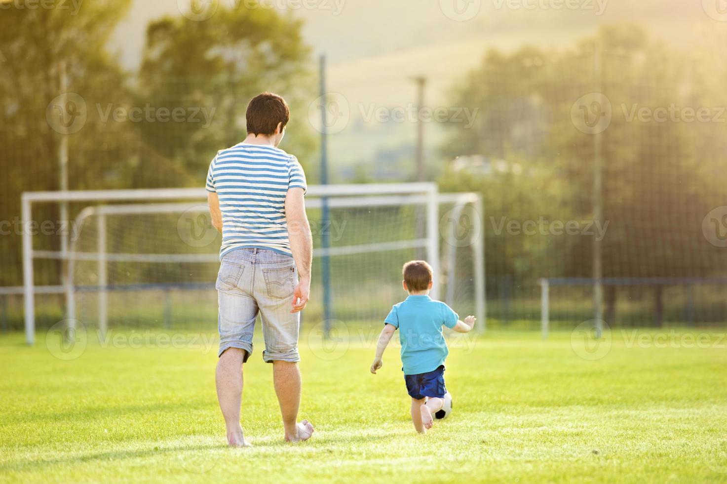 vader en zoon voetballen foto