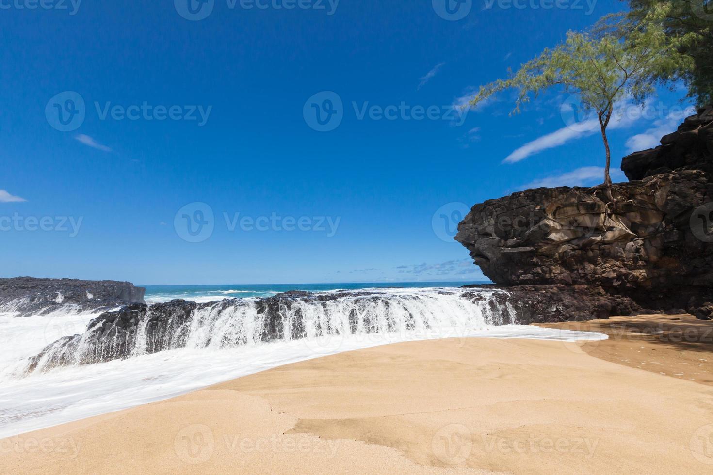 golven spatten over lavasteen op prachtige tropische zandstrand foto