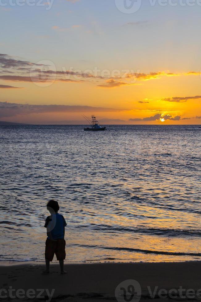 silhouet van een jonge jongen bij zonsondergang op Maui, Hawaii, Verenigde Staten foto