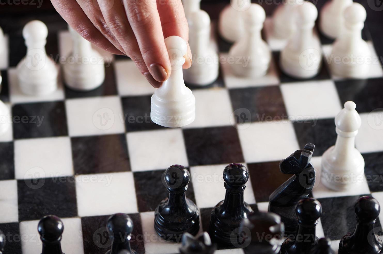 hand met witte pion over schaakbord foto