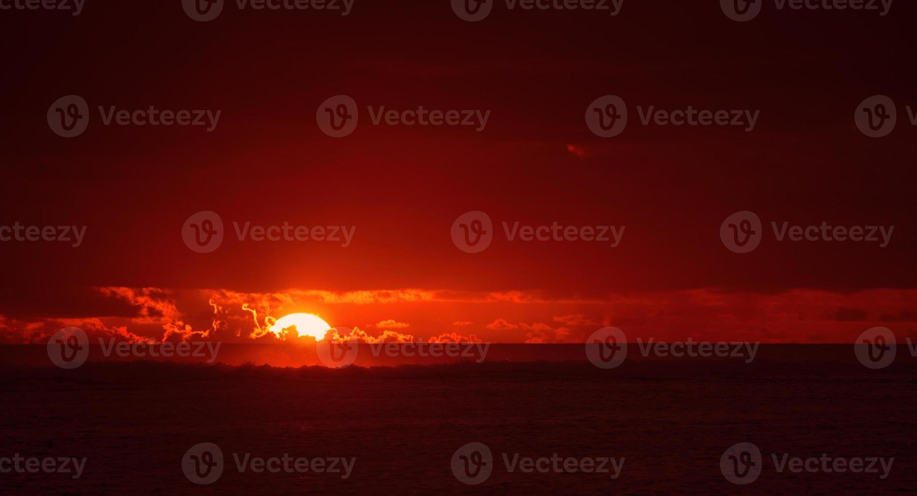 zon zinkt naar zee foto