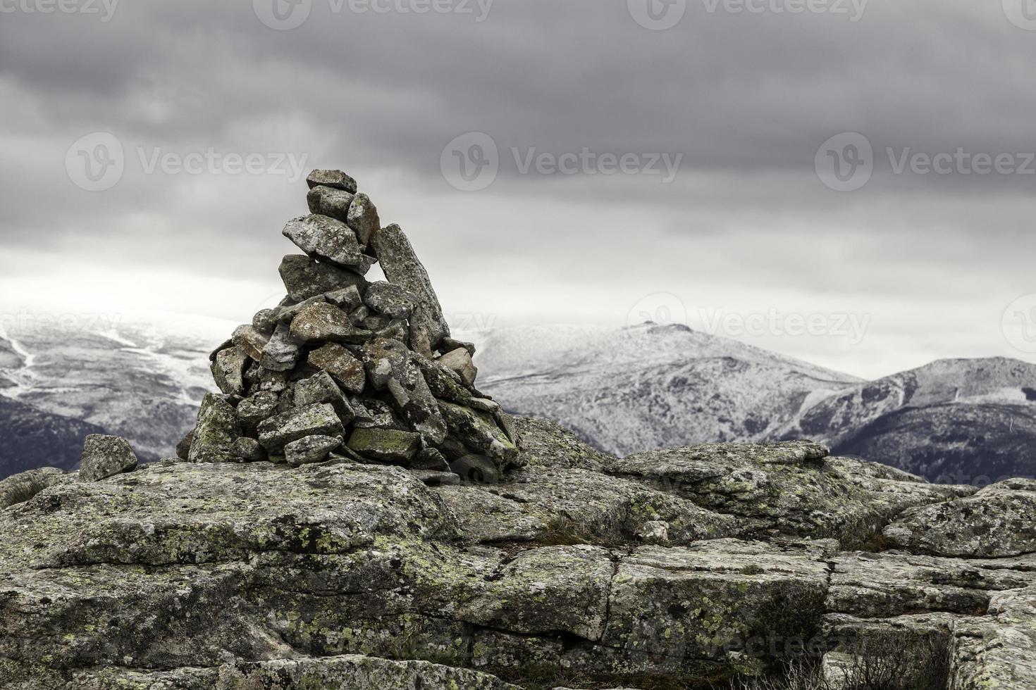 heuvelachtig landschap met een mijlpaal van stenen op de voorgrond foto