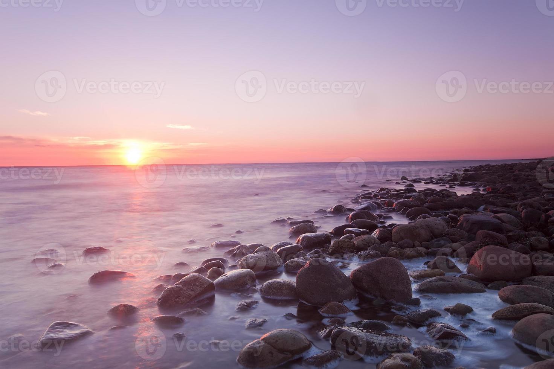 ondergaande zon over de Zweedse kust foto
