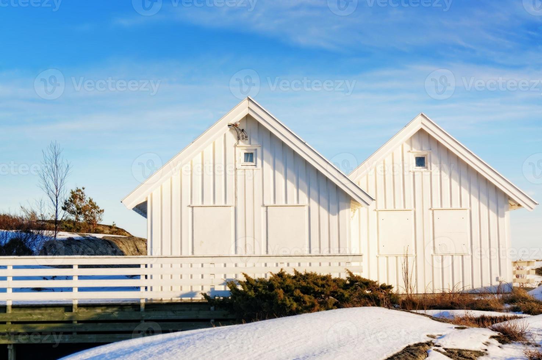 witte zomerhuisje, ramen met planken voor de storm foto