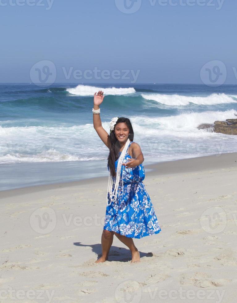 lachende tiener hula danser op een leeg strand foto