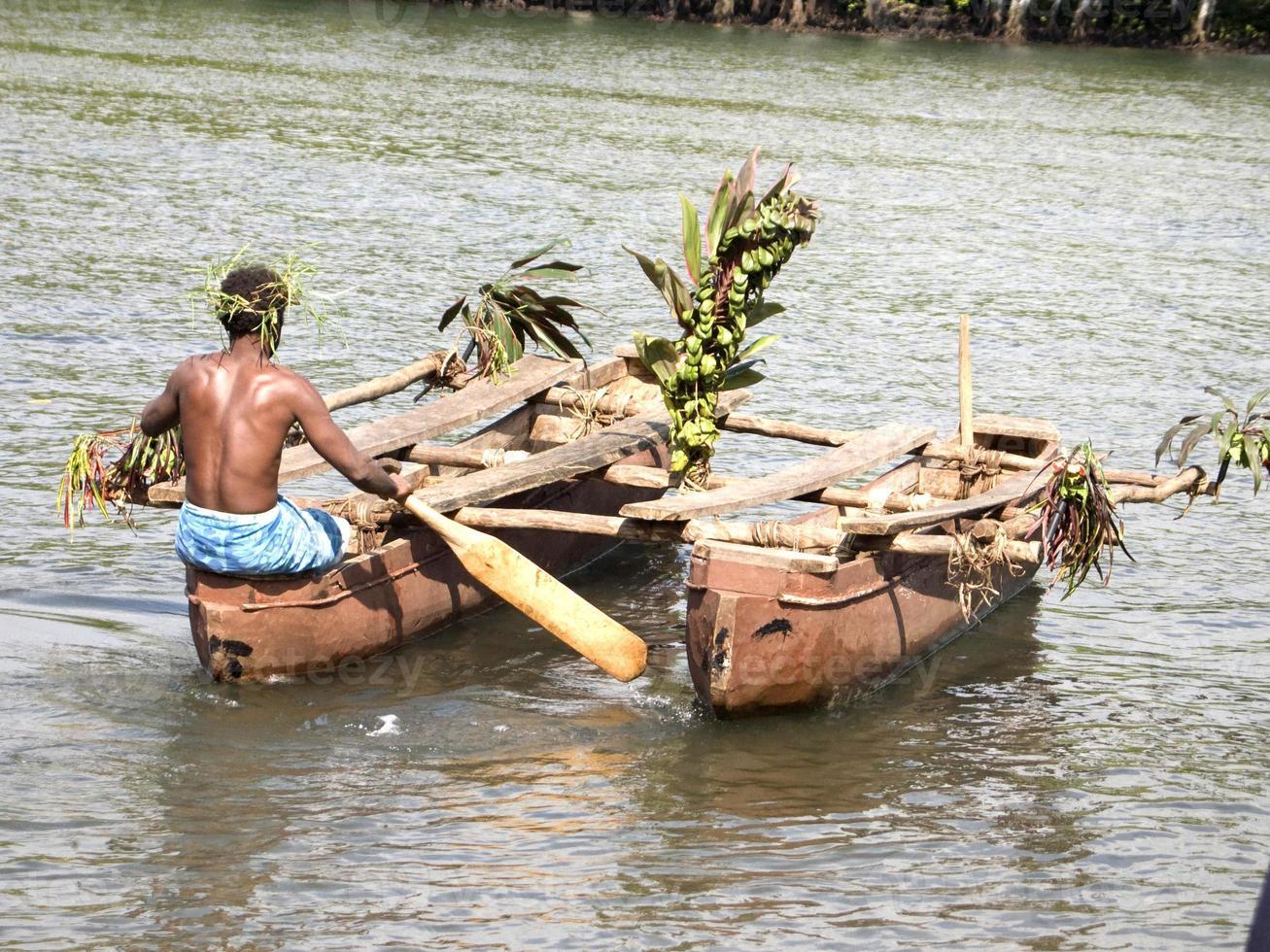 een tribale man die twee kano's duwt foto