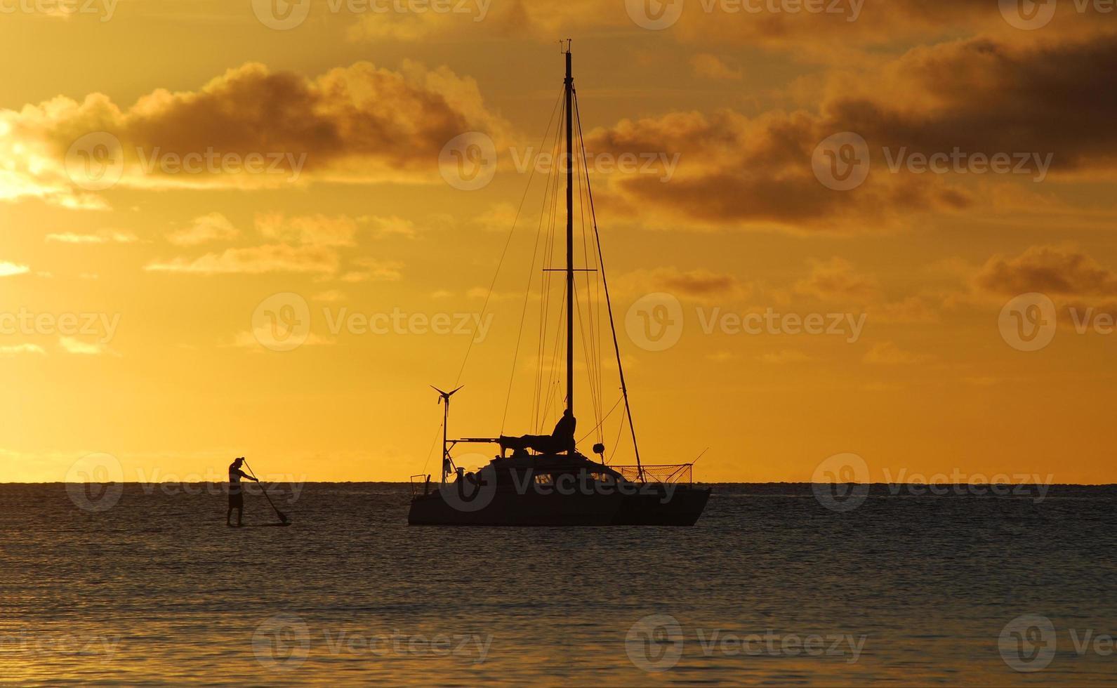 zonsondergang met catamaran en peddelboarder foto