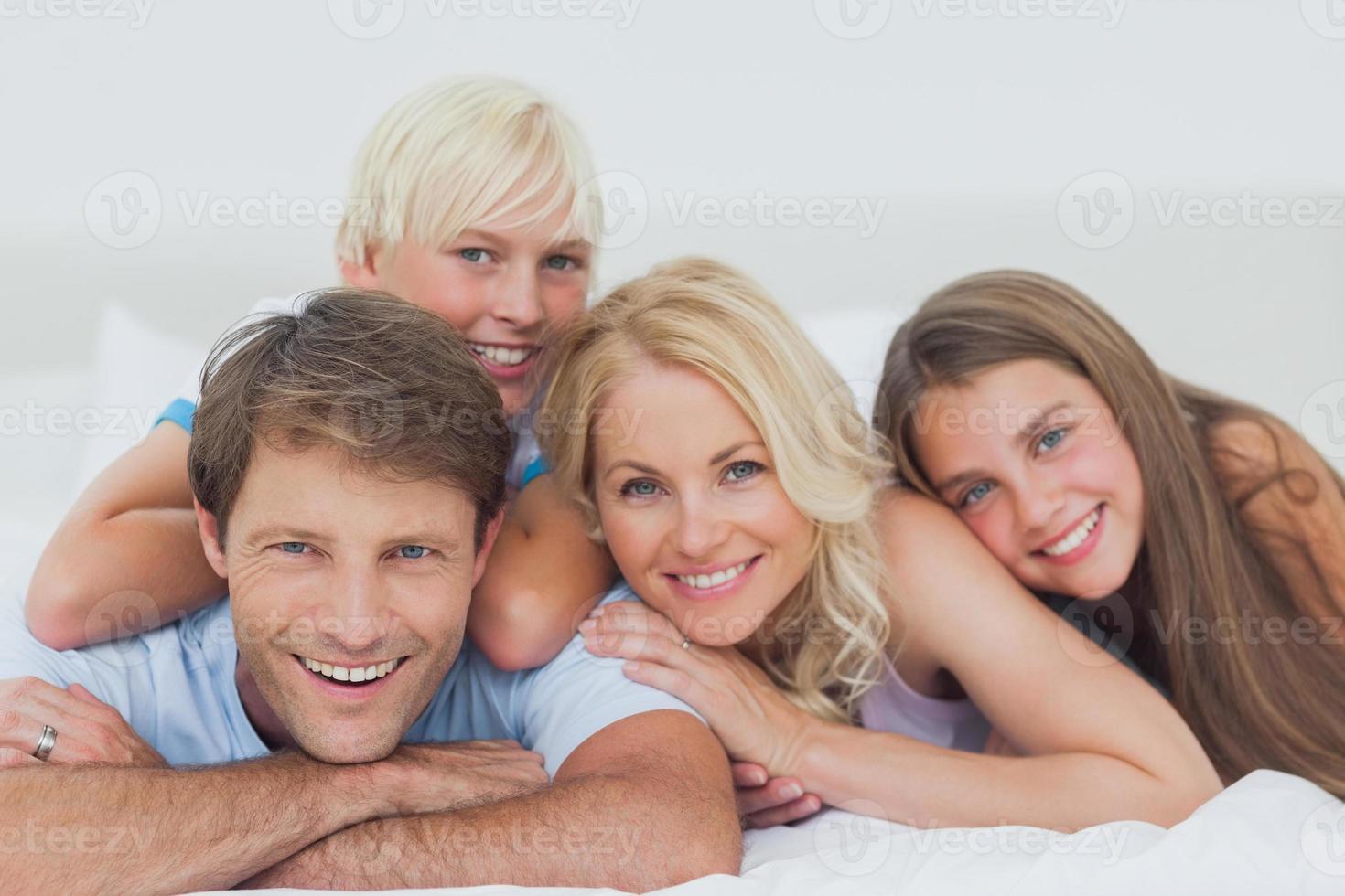 lachende familie liggend op bed foto
