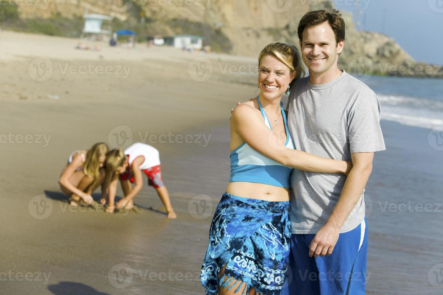 koppel met familie genieten van strand foto