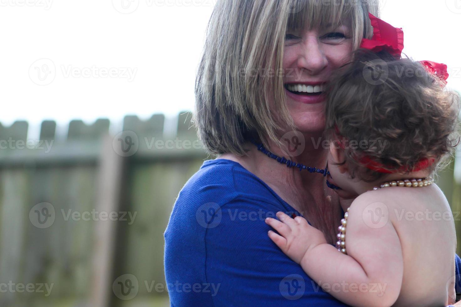glimlachende grootmoeder met haar kleindochter foto