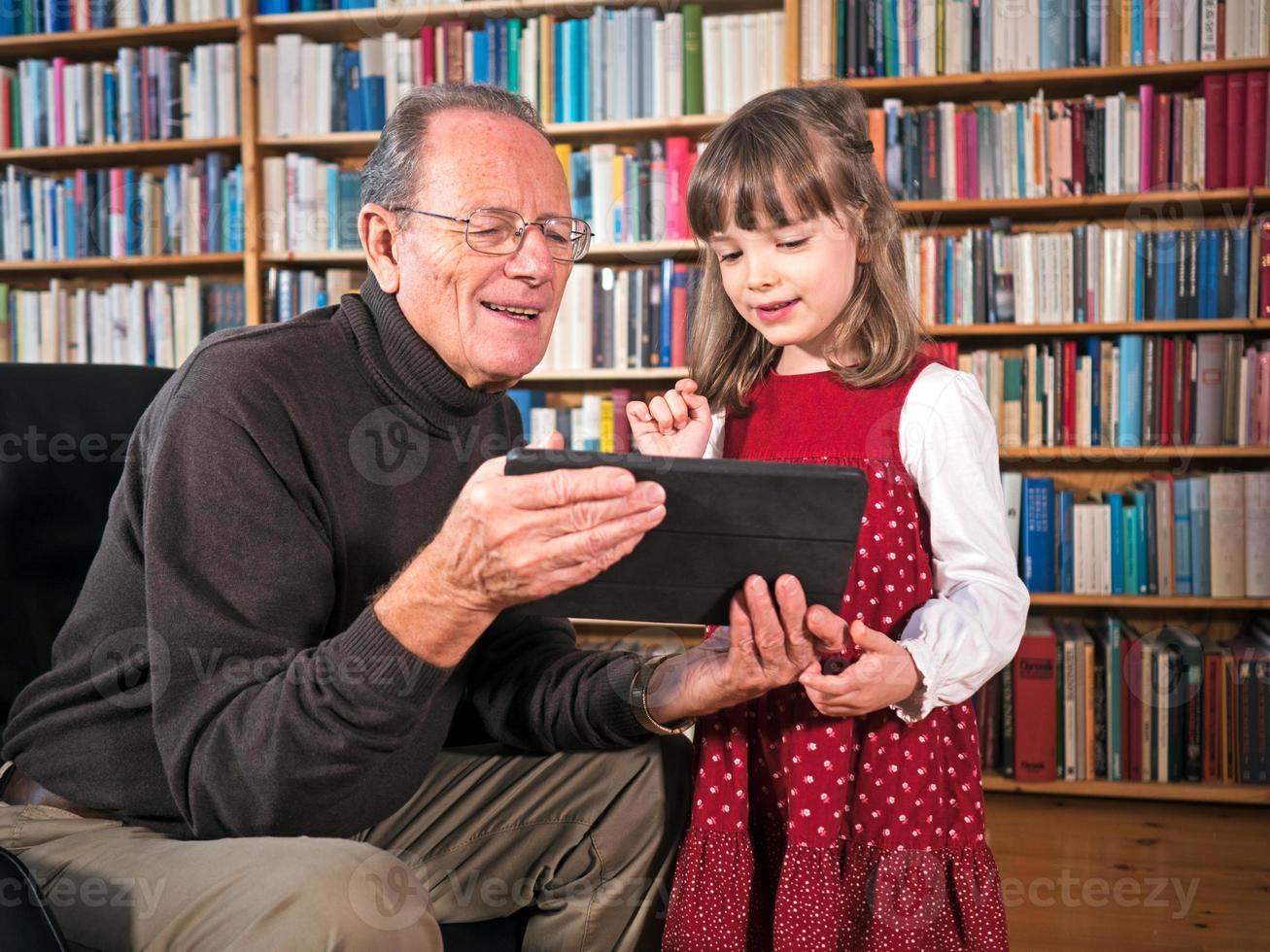 opa en kleindochter op zoek naar een tablet foto