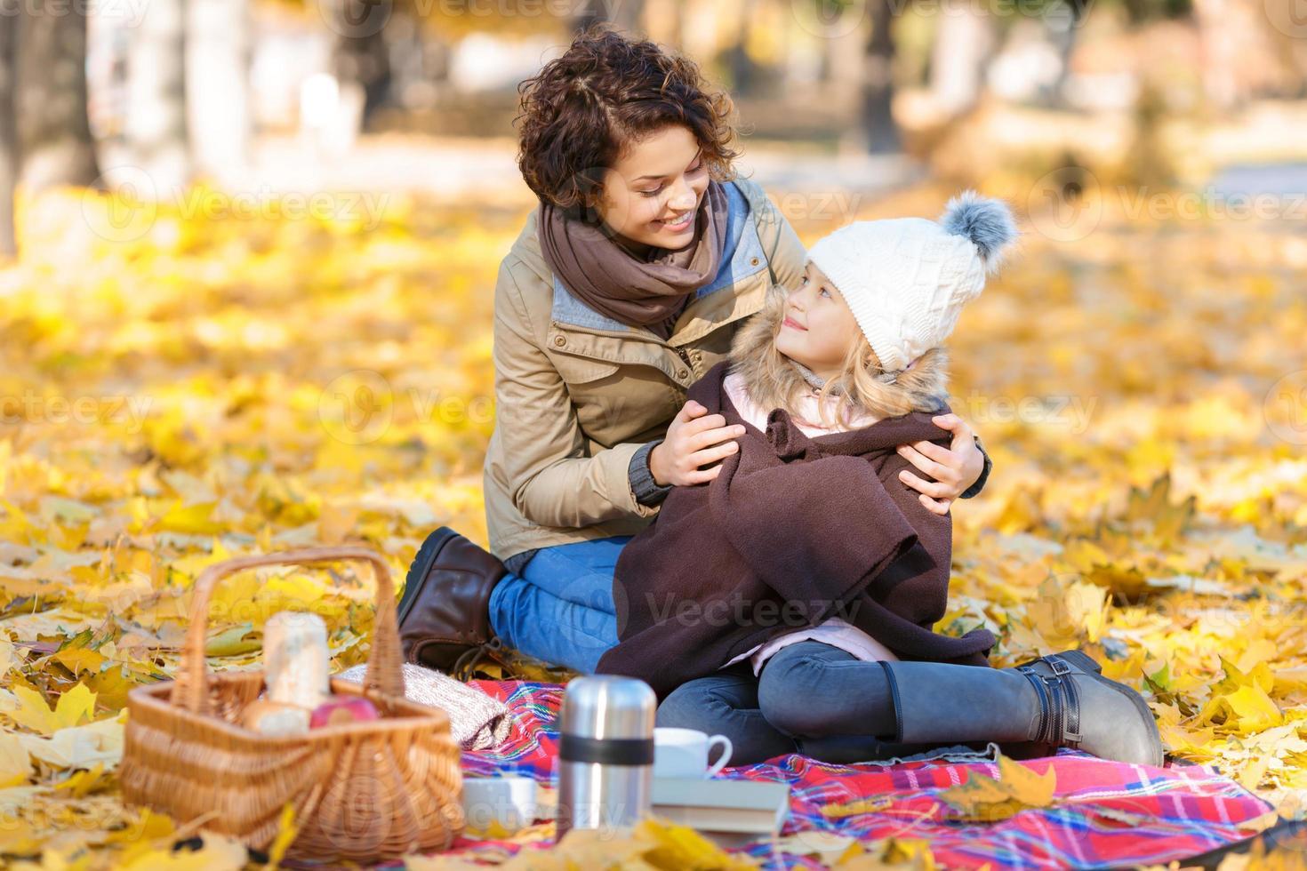 gelukkige moeder zittend op de deken met haar dochter foto