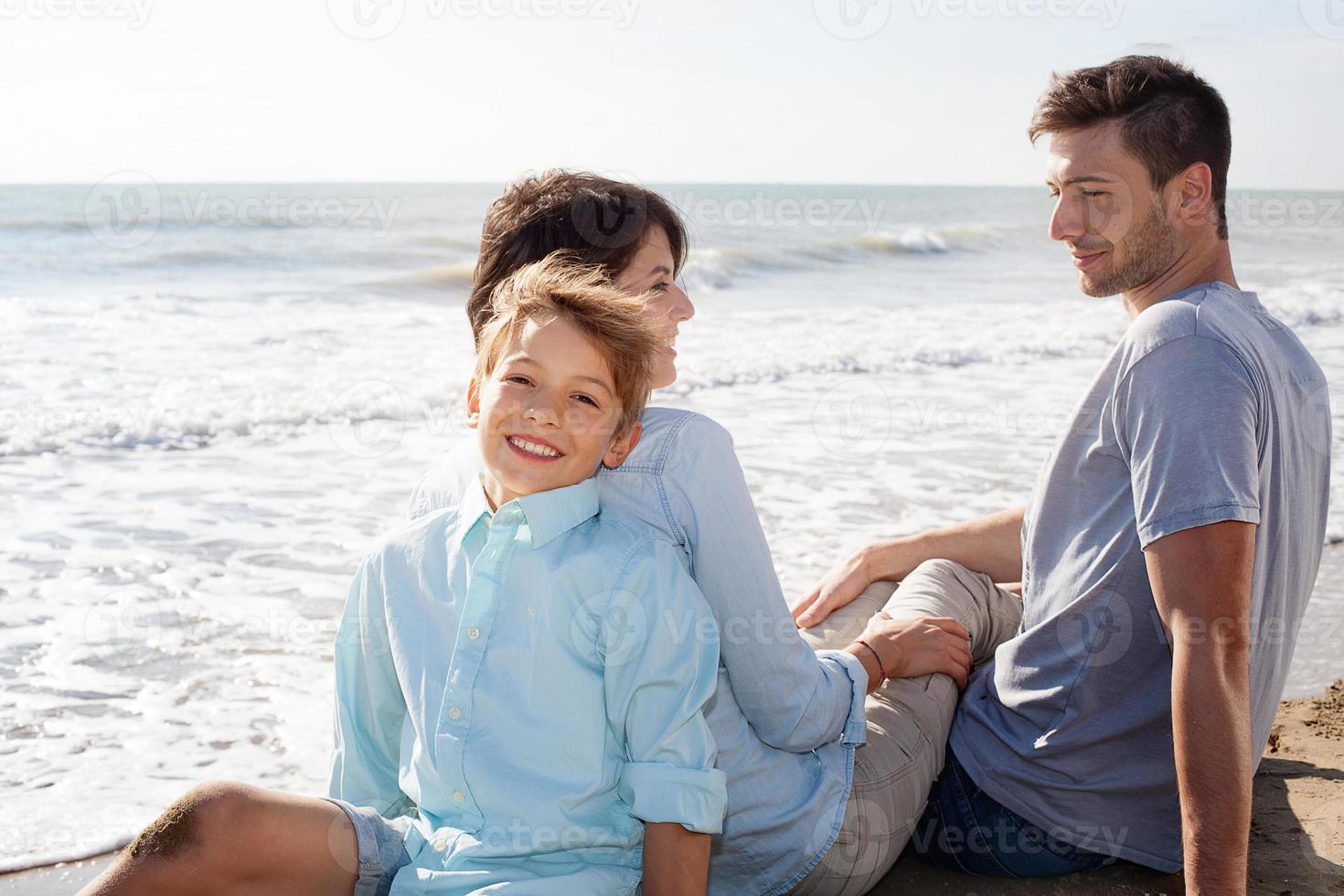 gelukkige familie zittend op het strand foto