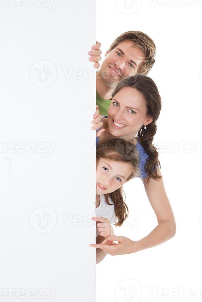 gelukkige familie gluren van leeg reclamebord foto