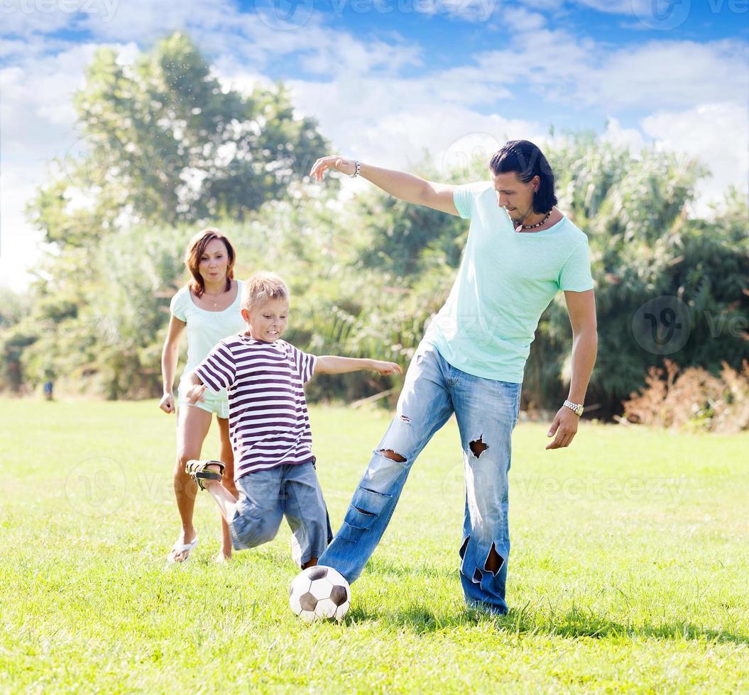 gezin van drie spelen met bal foto