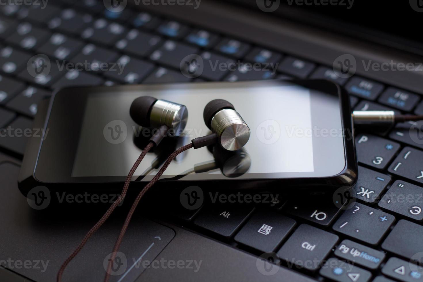 hoofdtelefoon en mobiele telefoon op het toetsenbord. foto