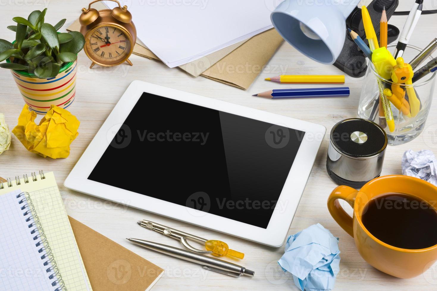 tabletcomputer in een puinhoop van het werk op bureau foto
