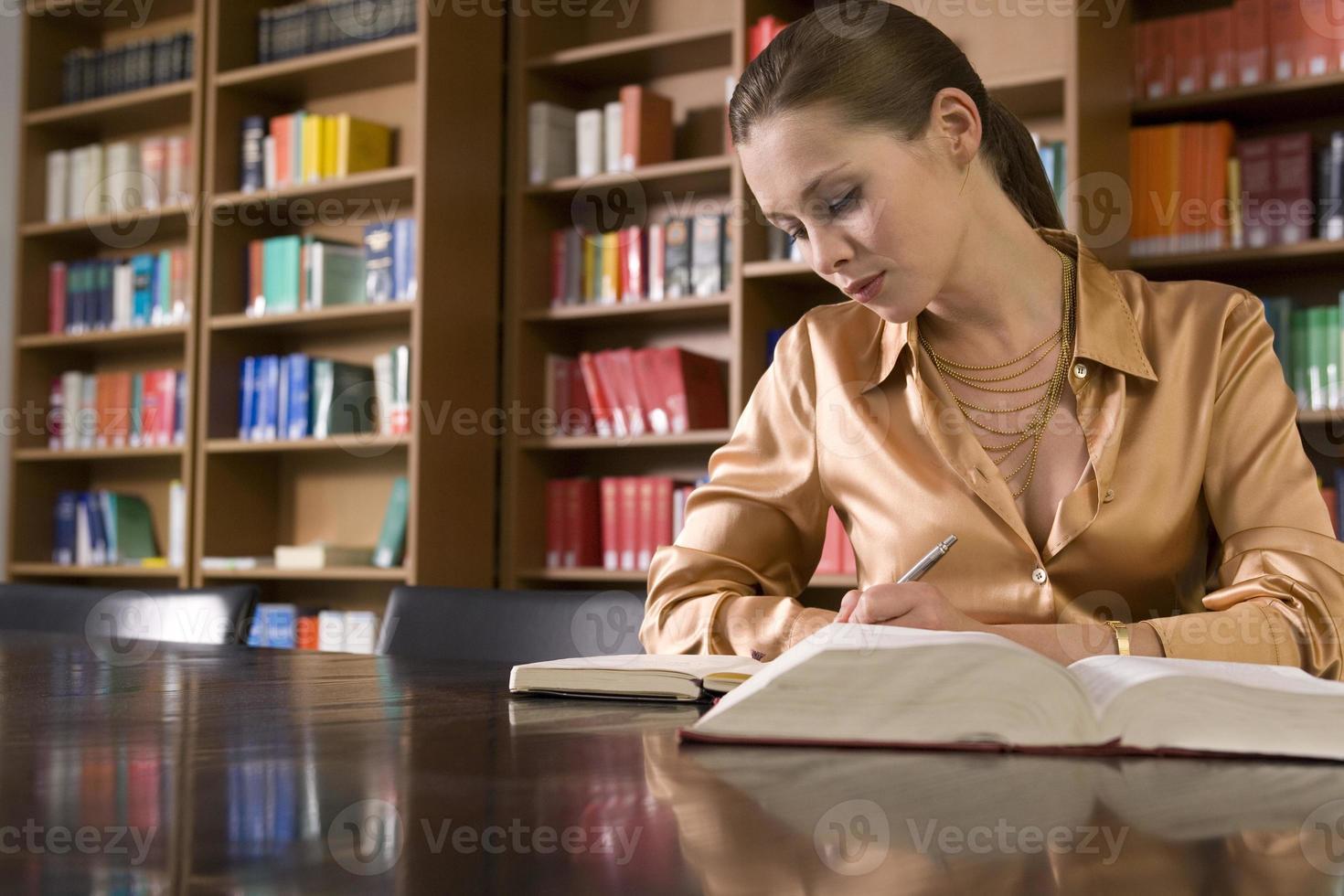 vrouw studeren aan balie in bibliotheek foto